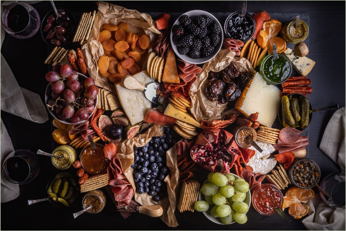 A giant charcuterie board with a variety of cured meats, cheeses, fruits, crackers and spreads.