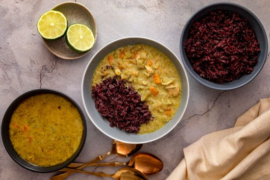 Thai green curry served with a mix of jasmine and black rice, with limes on the side
